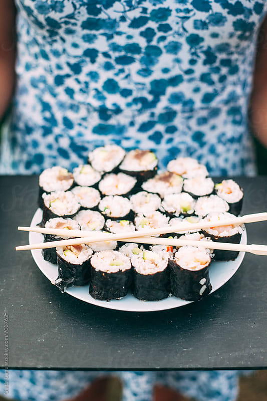 Woman holdin a plate full of Sushi by Giada Canu for Stocksy United