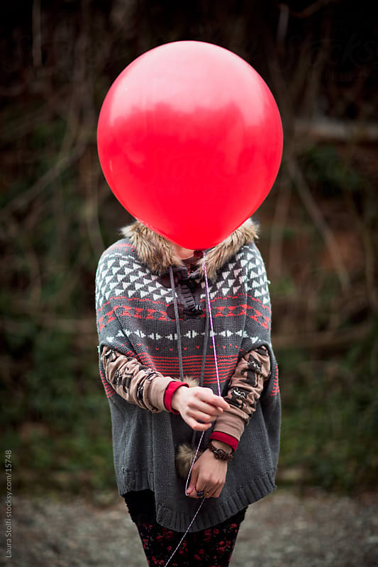 Woman hiding her face behind a red balloon by Laura Stolfi for Stocksy United