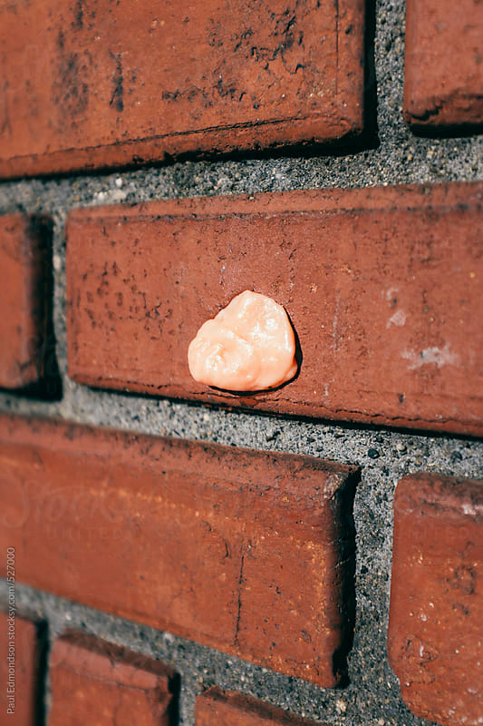 Discarded bubble gum on brick wall by Paul Edmondson for Stocksy United