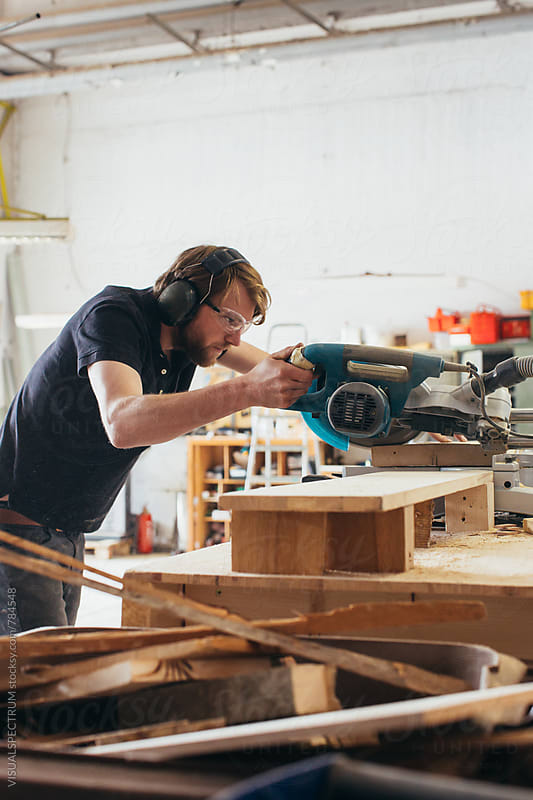 Male Carpenter Using Circular Saw in Bright Workshop by Julien L. Balmer for Stocksy United