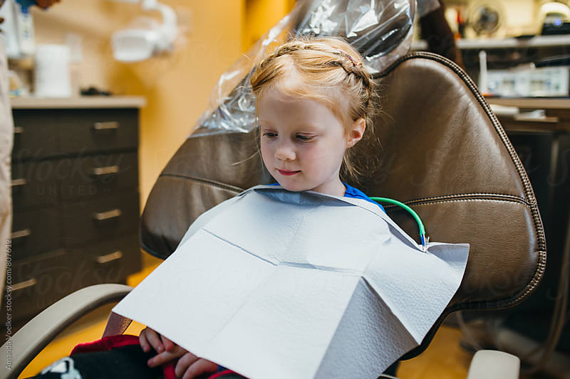A Little Girl sits in wait at the Dentist by Amanda Voelker for Stocksy United