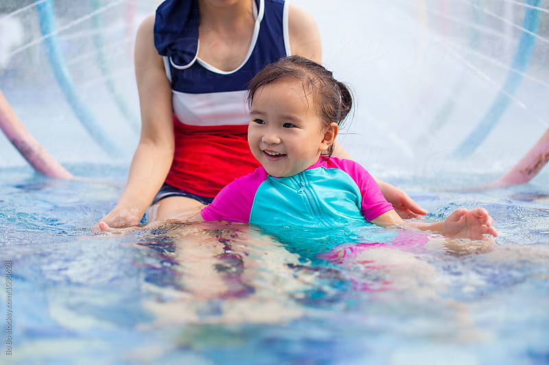 little girl in swimming pool with her mother by Bo Bo for Stocksy United