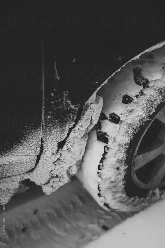 Studded tire on a car sprayed with snow by Jonas Räfling for Stocksy United
