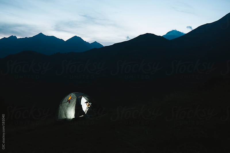 Man camping in the mountain at night by GIC for Stocksy United