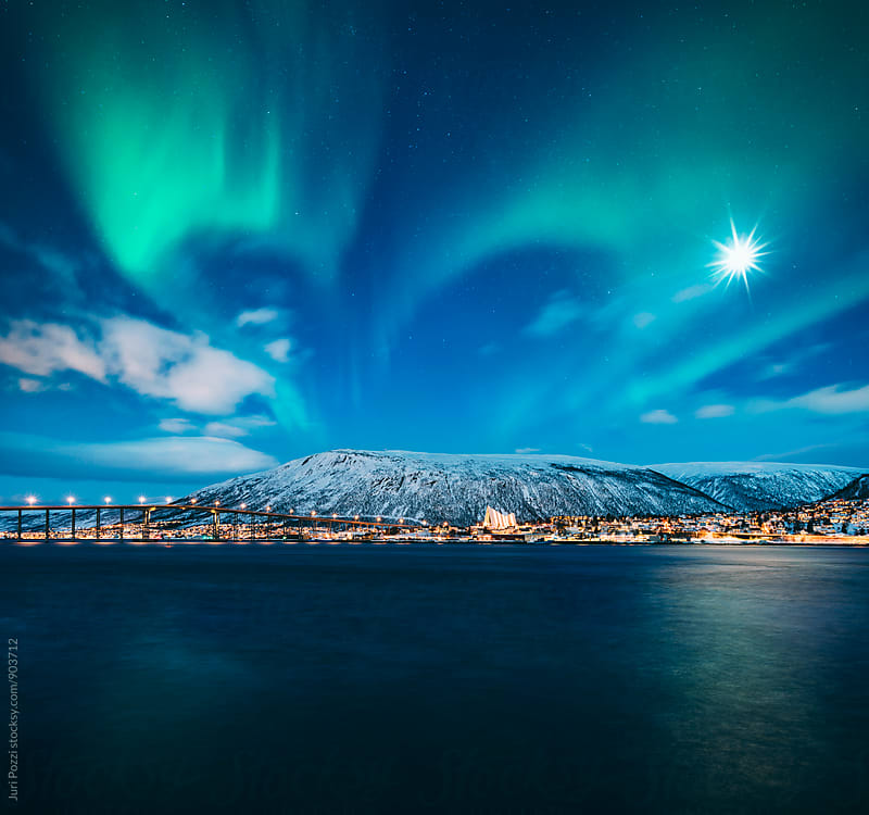 Northern lights over Tromso city in winter by Juri Pozzi for Stocksy United