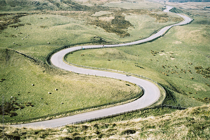 Cyclists on a curved mountain road below Mam Tor. Derbyshire, UK. by Liam Grant for Stocksy United