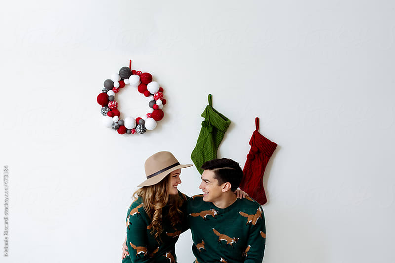 Holiday portrait of a young couple by Melanie Riccardi for Stocksy United