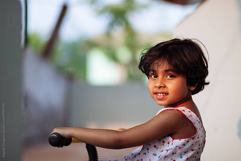 Portrait of smiling little girl on a tri-cycle by Saptak Ganguly for Stocksy United