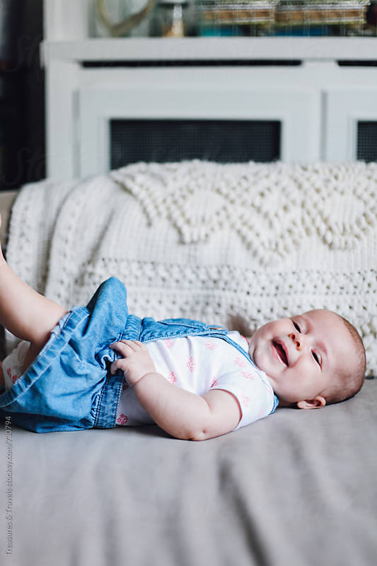 Cute baby laying on a couch by Treasures & Travels for Stocksy United