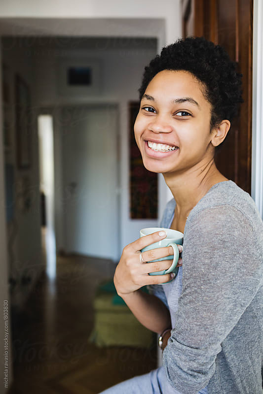Portrait of beautiful African woman holding a cup of coffee by michela ravasio for Stocksy United