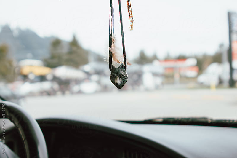 Feather Wolf Head Necklace Hanging From Car's Rear View Mirror  by Luke Mattson for Stocksy United