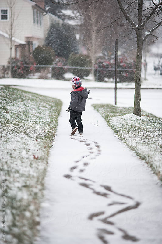 Boy making zig zag tracks in first snow of the season  by Cameron Whitman for Stocksy United