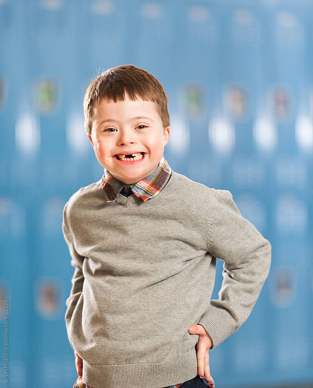 Elementary aged boy with Down Syndrom with School Lockers in Background by Brian McEntire for Stocksy United