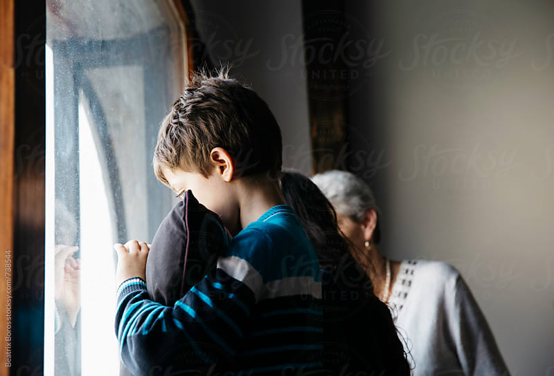 Boy holding his pillow by the window sadly waving bye to someone by Beatrix Boros for Stocksy United