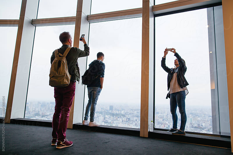 Tourist friends taking photos of Tokyo skyscraper.  by BONNINSTUDIO for Stocksy United