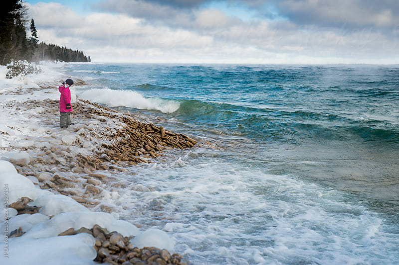 Little Girl Watching the Waves On Freezing Cold Winter Lakeshore by JP Danko for Stocksy United