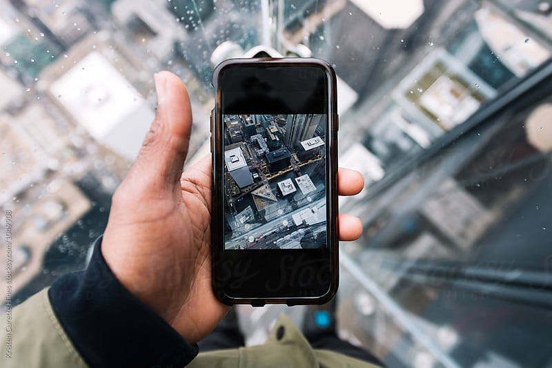 Someone taking a photo with their mobile phone of glass balcony at the Skydeck of the Willis Tower Chicago,Illinois by Kristen Curette Hines for Stocksy United