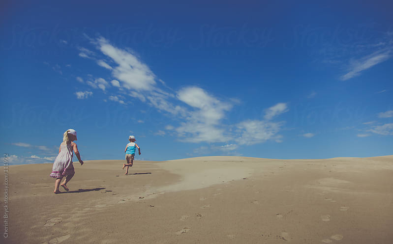 Two little girls run though the vast sand dunes. by Cherish Bryck for Stocksy United
