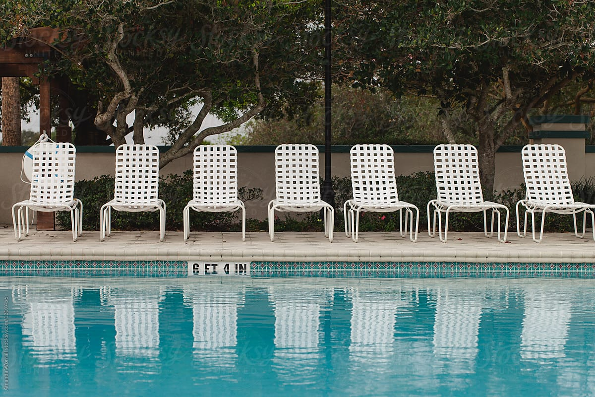 A row of empty lounge chairs reflecting into a swimming pool ...