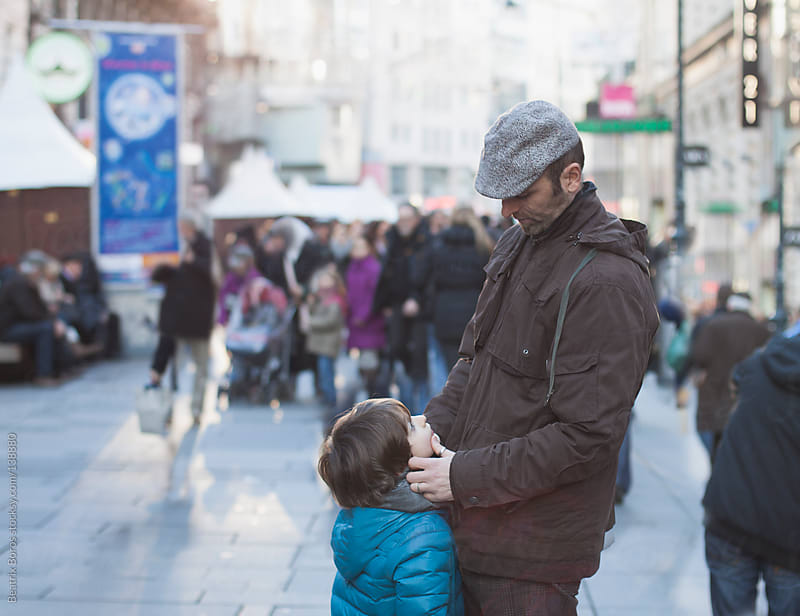 Boy looking up at his father in the street by Beatrix Boros for Stocksy United