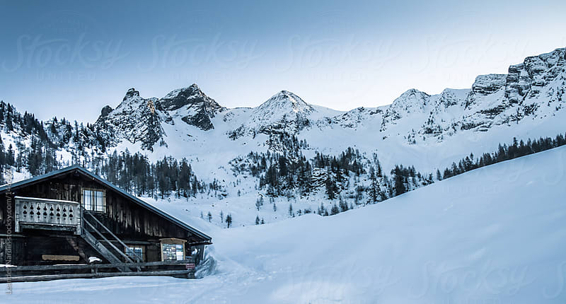 Panorama view to snowcovered big mountains with a alpine cabin in the alps by Leander Nardin for Stocksy United