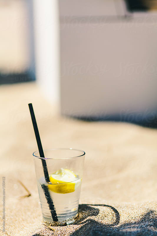 Summer cocktail - tonic and lemon with black straw in the sand by Borislav Zhuykov for Stocksy United