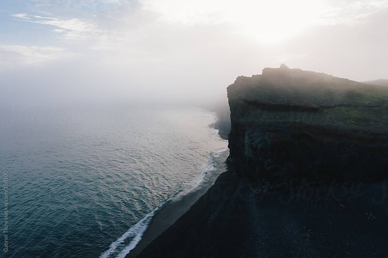 Foggy coast with black sand beach by Gabriel Tichy for Stocksy United