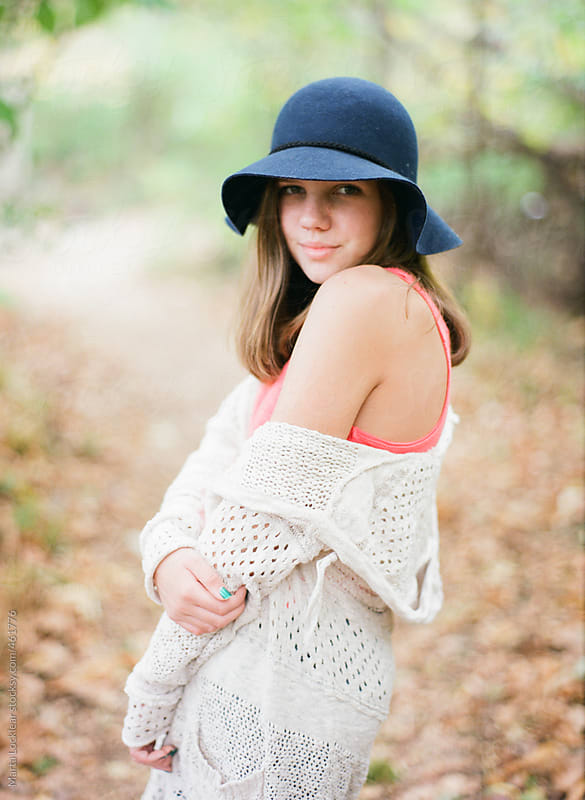 Teen girl in a blue hat looking back and smiling by Marta Locklear for Stocksy United