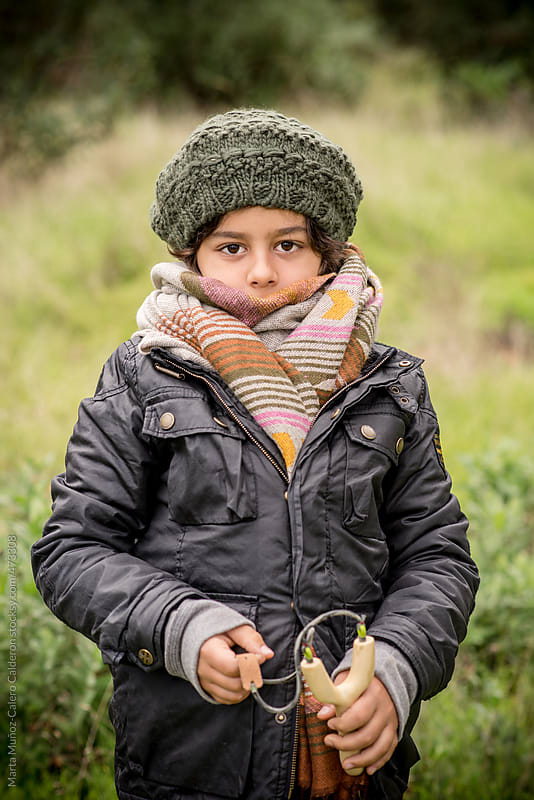 Boy with big scarf and wool hat in the woods by Marta Muñoz-Calero Calderon for Stocksy United