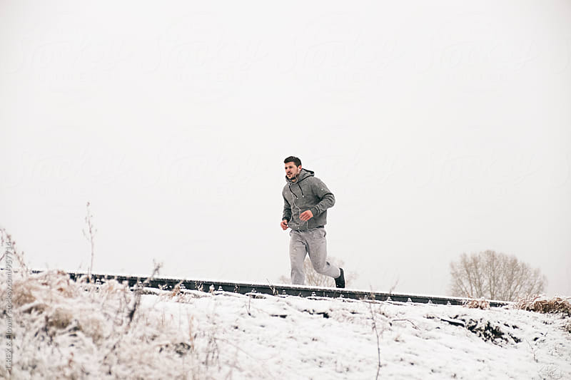 Energetic man running in winter by Danil Nevsky for Stocksy United