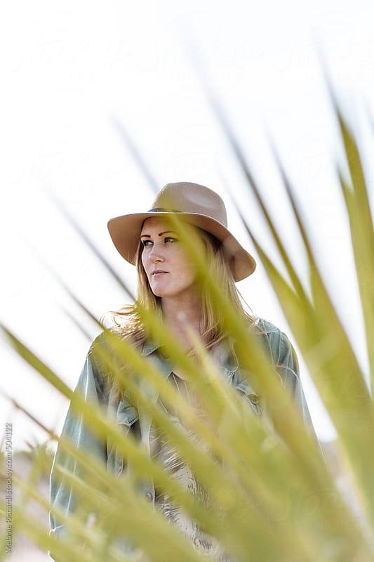 Woman portrait in desert wearing a hat by Melanie Riccardi for Stocksy United