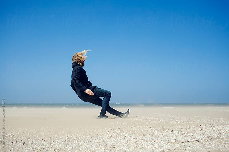 Young man leaning against the strong wind on the beach and falls down by Denni Van Huis for Stocksy United