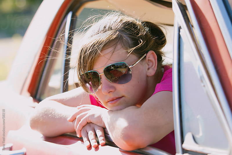 A teenager wearing sunglasses hangs out an old car window by Tana Teel for Stocksy United