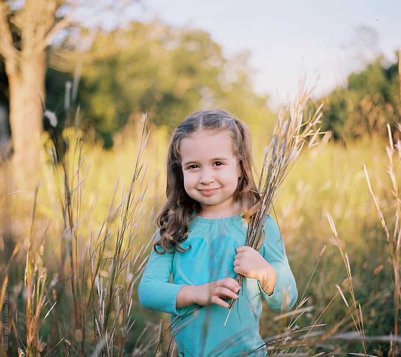Portrait of a beautiful young girl holding tall grass in a field by Jakob for Stocksy United