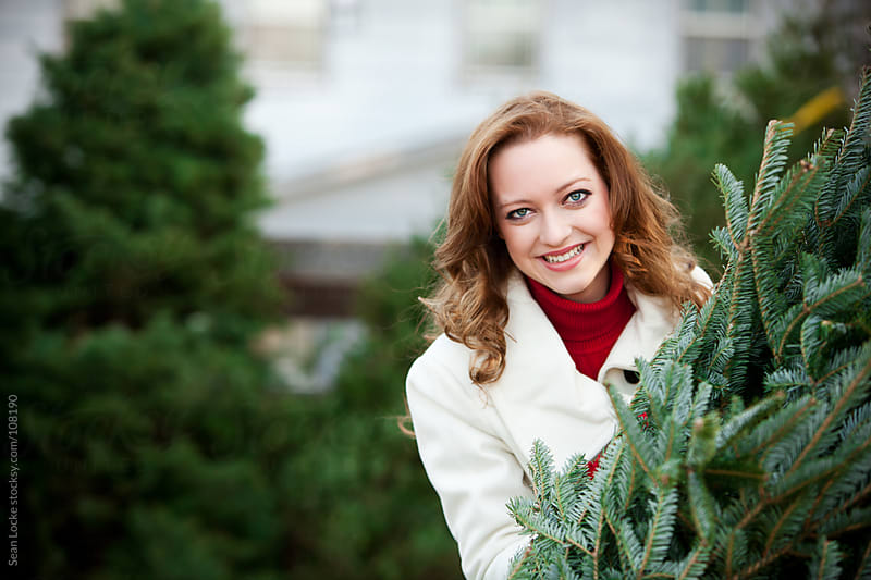 Tree Lot: Woman Standing With Christmas Tree by Sean Locke for Stocksy United