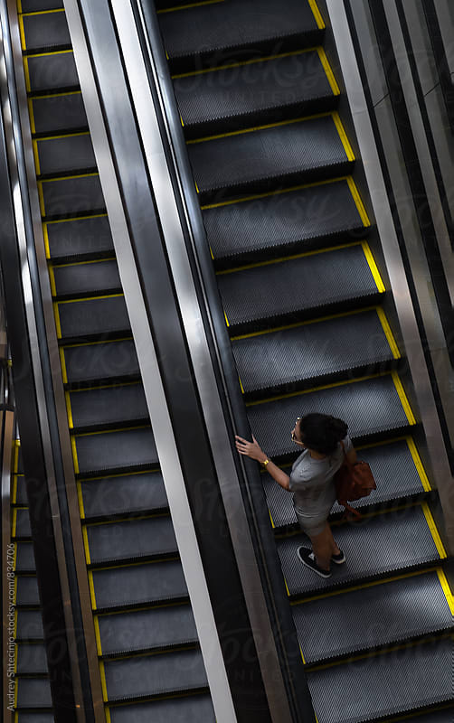 Young stylish woman on one of many escalator stairs/look from above. by Audrey Shtecinjo for Stocksy United