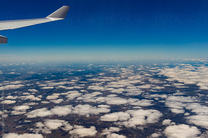 Airplane wing and puffy little clouds over Australia by Angela Lumsden for Stocksy United