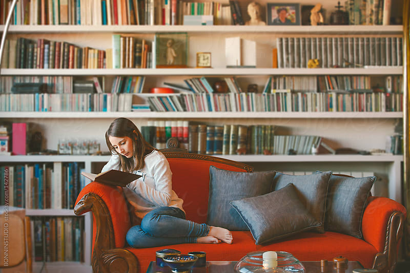 Young woman reading a book on a beautiful vintage couch at home. by BONNINSTUDIO for Stocksy United