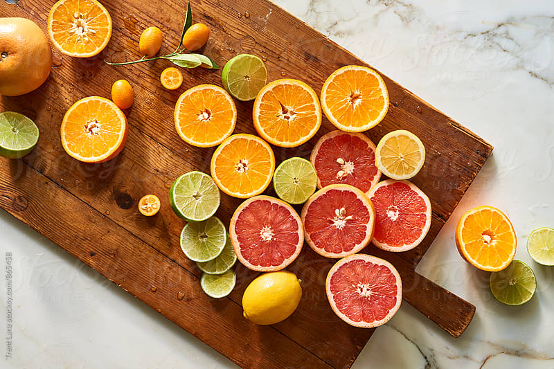Oranges, lemons and limes citrus on wooden cutting board by Trent Lanz for Stocksy United