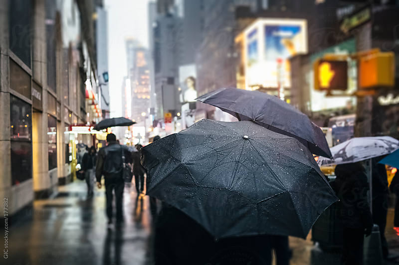 People holding umbrella under the rain in Times Square - NYC by GIC for Stocksy United