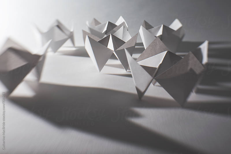 Folded white paper fortune tellers by Catherine MacBride for Stocksy United
