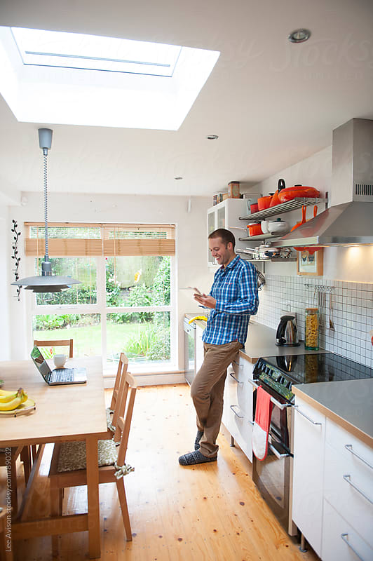 man using a digital tablet in his kitchen by Lee Avison for Stocksy United