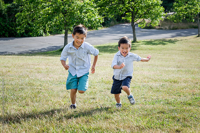 Asian kids running outdoor in a park by Suprijono Suharjoto for Stocksy United