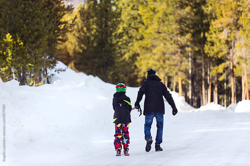 Father towing his son on skis on a snow-covered road, viewed from behind by Angela Lumsden for Stocksy United