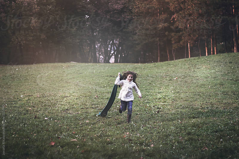 Little girl running with scarf in her hand in park  by Jovana Rikalo for Stocksy United