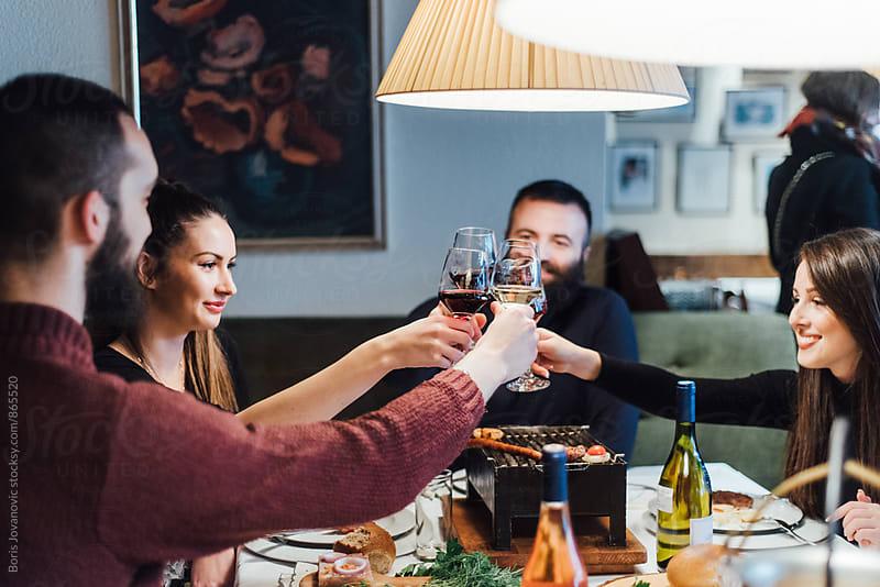 Friends having a toast in the restoraunt by Boris Jovanovic for Stocksy United