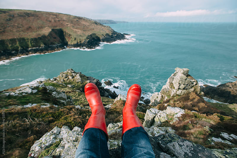 Feet looking over cliff by Aila Images for Stocksy United