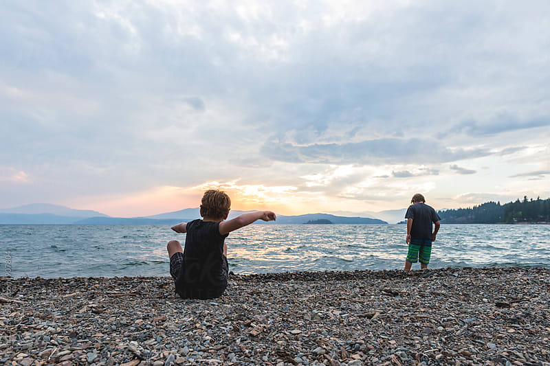 Boys skipping rocks enjoying beautiful view on sunbeam through cloudy sky by Trent Lanz for Stocksy United