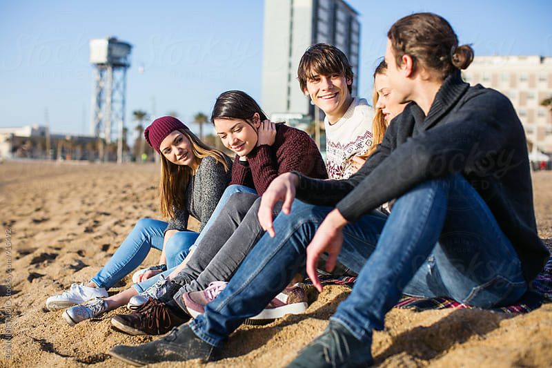 Teenage friends hanging out sitting on the beach. by BONNINSTUDIO for Stocksy United
