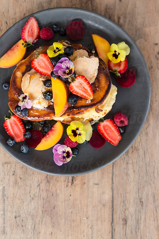 overhead of pancakes with a generous amount of fresh, seasonal fruit, and edible flowers, with copyspace by Gillian Vann for Stocksy United